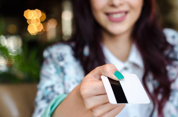 девушка вручает пластиковую карту